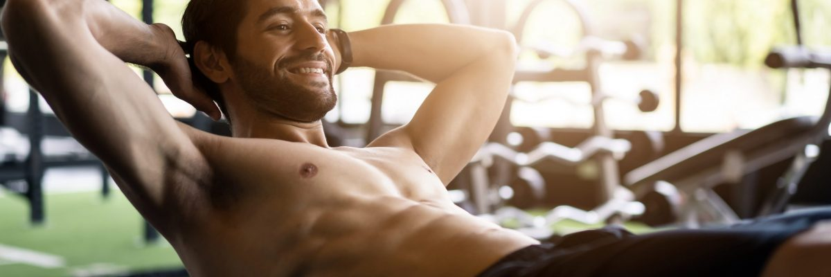 Young handsome smiling Caucasian man with beard and shirtless exercising by doing a sit-up on bench in gym or fitness club. He has a good body shape with six pack. Sport recreation and fitness concept